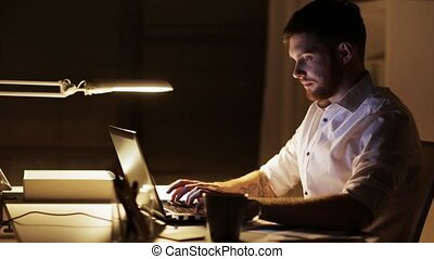 man with laptop and smartphone working at night office -...