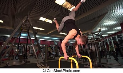 Bodyweight exercise, man standing on hands at gym using the...