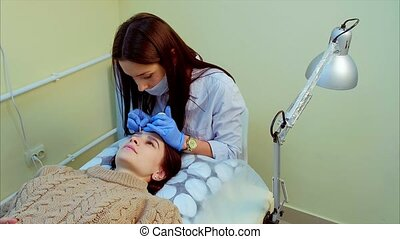 Beautician making permanent makeup of eyelash. - Applying...