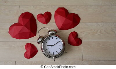 Big alarm clock with red polygonal paper heart shapes over...