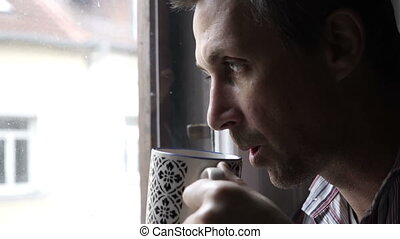 Man Looking Out Window Drinking Coffee - Handheld shot of a...