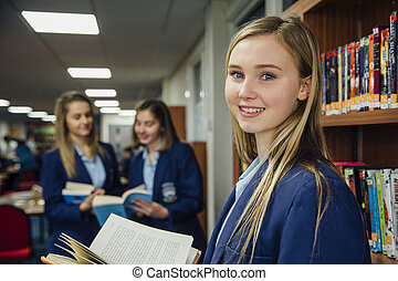 Reading In School Library - Teenage girl is standing in the...