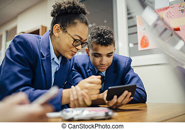 Sneaky Students Using Smartphone In Lesson - Two teen...