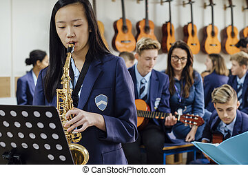 Playing The Saxaphone - Teen student is playing the...