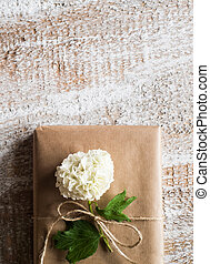 Present wrapped in brown paper, lilac flower laid on it.