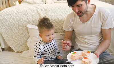 Little adorable boy celebrating his birthday with young father eat cake in bedroom