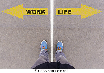 Work vs Life text arrows on asphalt ground, feet and shoes...