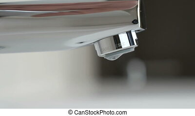 Strong stream of water flows from chrome faucet