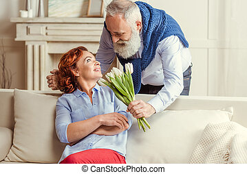 Mature couple with flowers - Mature bearded man gives...