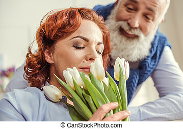 Mature couple with flowers - Mature woman holding bouquet of...