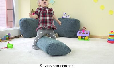 Active toddler girl climb on blue huge pillow and show true...