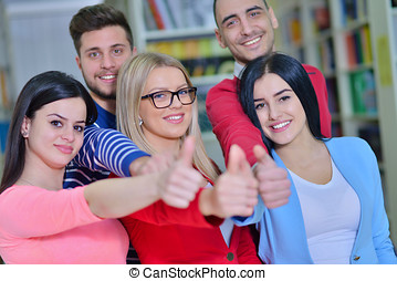 Cheerful group of students smiling at camera with thumbs up,...