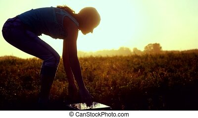 Young pretty caucasian woman typing on a laptop outdoors at beautiful sunset sitting on the grass with amazing lense flare effects in summer time.