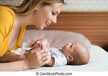 Mother with her newborn baby son lying on bed