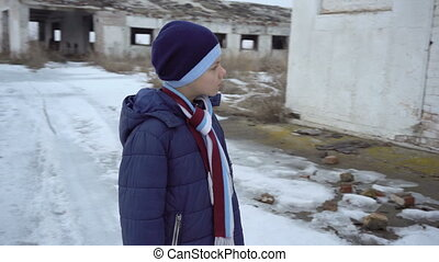 A boy stands near a collapsed farm in winter. Circling...