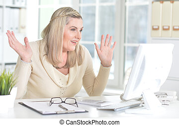 mature woman using computer - Portrait of an excited mature...