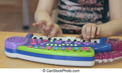 Child little girl playing on a toy piano. Close-up