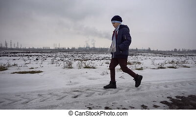 Boy walking on frozen road - The boy is in the winter on...