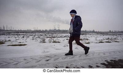 Boy walking on frozen road - The boy is in the winter on...