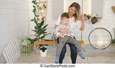 Happy young mother with her little son sits on rope swing and play together in their bedroom