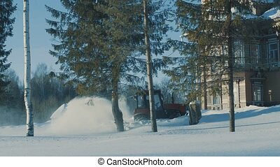 Tractor driving backwards and removing snow from the winter road near terem