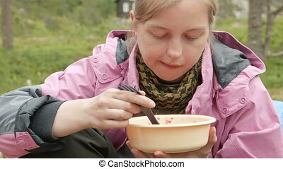 Girl eats soup outdoors during the rest of the hiling