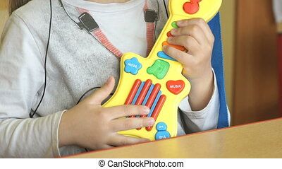 Child playing on toy guitar at kindergarten. Close-up