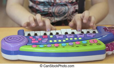 Little girl playing on a toy piano in kindergarten. Close-up