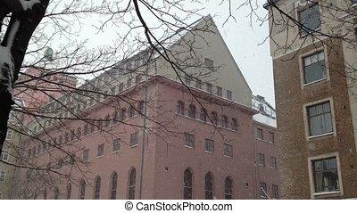 Snowfall in a city at winter