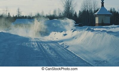 Tractor driving backwards and removing snow from the winter road