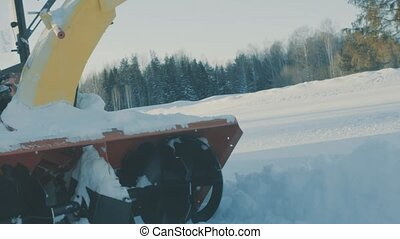 Tractor riding on the snow road. Winter forest on background.
