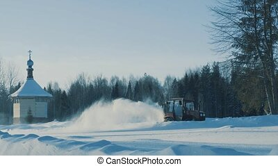 Tractor driving backwards and removing snow from the winter...