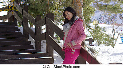 Woman in pink snowsuit relaxing on stairs - Smiling young...