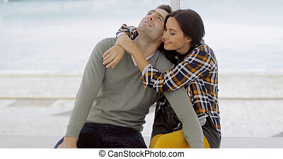 Loving young woman hugging her boyfriend who is relaxing...