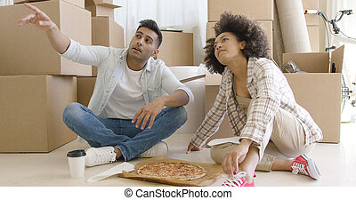 Young couple eating pizza and chatting - Young couple eating...
