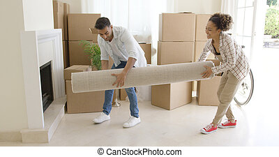 Young couple carrying a rolled rug into a house