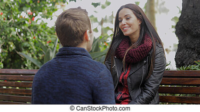Young man squatting down talking to his girlfriend - Young...