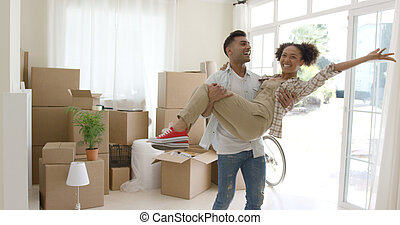 Ecstatic young couple celebrating their new home with the...