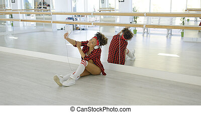 Dancer with head phones and wearing shorts takes photo of...