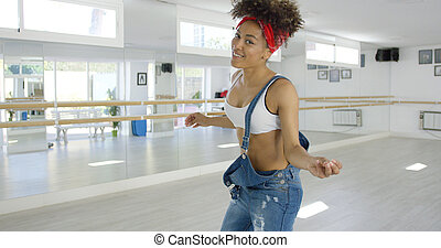 Attractive female dance student smiles at camera while...