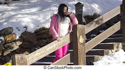 Adorable asian girl standing on wooden stairs in mountain...