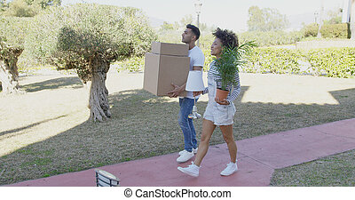 Young couple moving house carrying boxes and a potted...