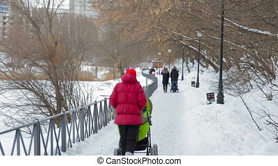 Woman walking with a baby carriage in winter park