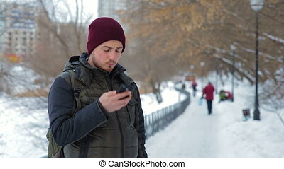 Man talking on cellphone in the park at winter time