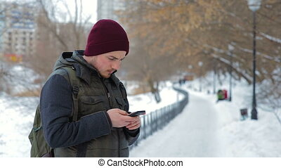 Young man using his smartphone outdoors