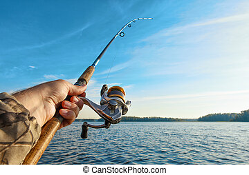 fishing on a lake at sunrise. Fishing rod with a reel in...