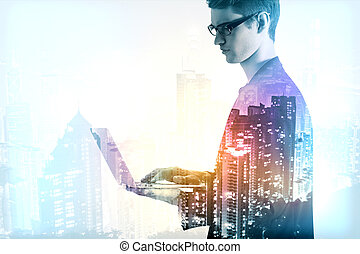 Communication concept - Young businessman using laptop on...