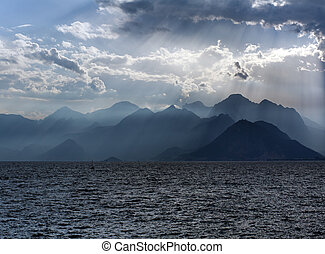 Scenery of sea and mountains on background of sky in sun rays