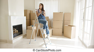 Young woman sitting on a stepladder