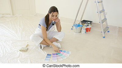 Young woman renovating or decorating her new home sitting on...